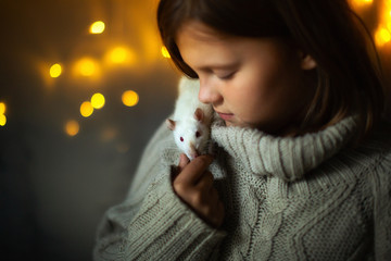 Girl with pet rat, garland lights and gray wall