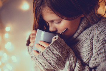 girl child in sweater with cup, cozy , toning