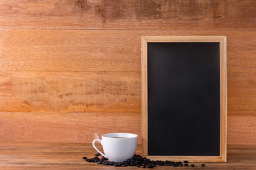a cup of coffee and blank chalkboard on wooden table