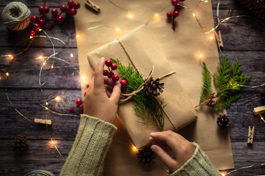 hands wrapping gift in craft paper, christmas mood