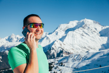 Handsome young male taking a picture with his smartphone. Mont Blanc in the background.