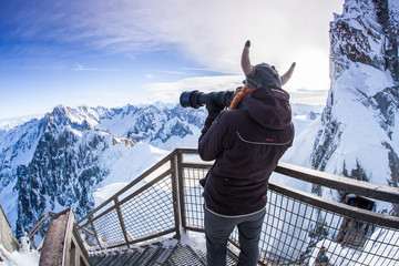 Woman with viking hat taking pictures in the French Alps.