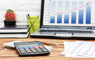 Financial documents, calculator, money and laptop on the office desk. Business report.
