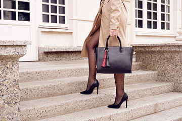 Wall Mural - Fashion woman on stairs in high heel shoes with black bag.