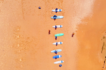 Aerial topshot from surferstraining on the beach at the atlantic ocean