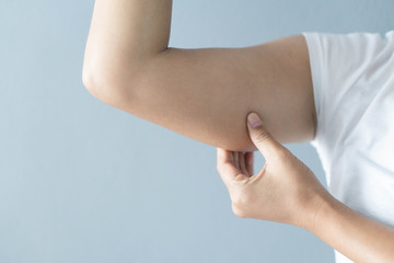 Closeup woman hand checking upper arm on grey background health care and medical concept