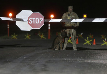 Military personnel with dogs guard a gate to Area 51 as an influx of tourists responding to a call to 'storm' Area 51, a secretive U.S. military base believed by UFO enthusiasts to hold government secrets about extra-terrestrials, is expected in Rachel, Ne