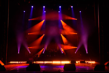 Lights beams on stage with musical instruments