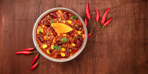 Tuinposter Hot chili peppers Chili con carne with chilli peppers and a nacho chip, overhead panoramic shot on a dark rustic wooden background with a place for text