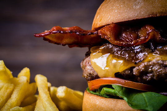 Craft beef burger with cheese, bacon, rocket leafs, caramelize onion and french fries on wood table and rustic background.