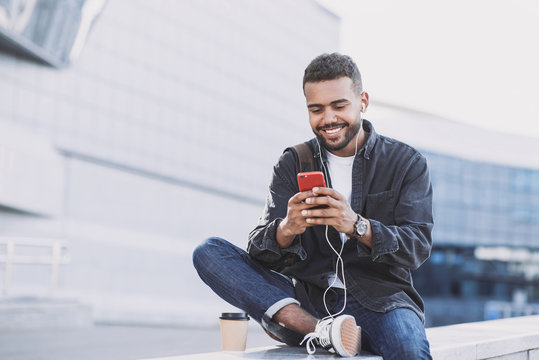 Young handsome men using smartphone in a city. Smiling student man texting on his mobile phone. Coffee break. Modern lifestyle, connection, business concept