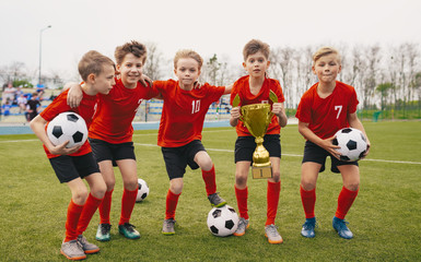 Happy Junior Sports Team. Young Boys in Soccer Team Holding Golden Cup and Soccer Balls. Group of children Winning School Sports Tournament. Schools Football Championship for Kids