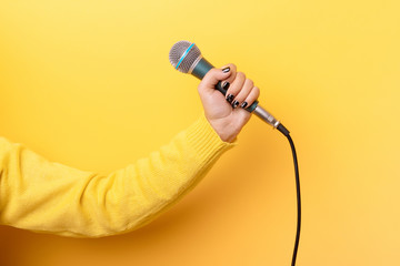 hand holding microphone over yellow background