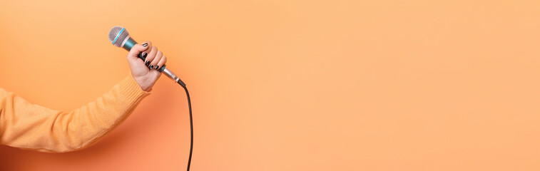 hand holding microphone over orange background, panoramic mock up image