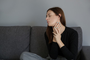 A picture of a young woman suffering from a sore throat or thyroid problem symptoms