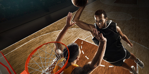 Two players playing basketball near the hoop. High angle view from the basketball rim