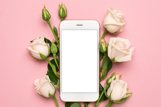 Mobile phone with roses flowers on pink pastel background, women technology concept