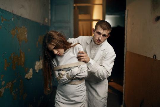 Psychiatrist leads female patient in straitjacket