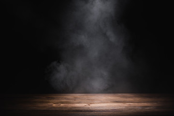 empty wooden table with smoke float up on dark background Fotobehang