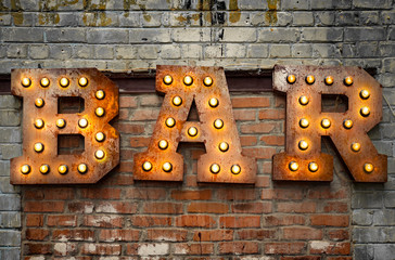 Inscription from large metal letters decorated with glowing light bulbs on the brick wall