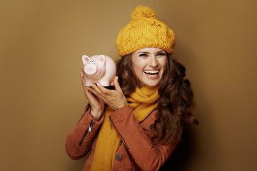 happy trendy woman showing piggy bank on bronze background