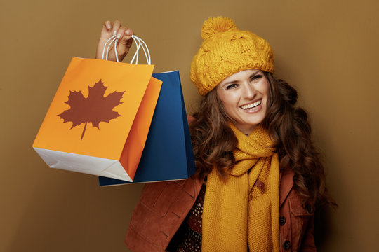 woman showing autumn shopping bags against bronze background