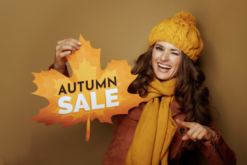 woman pointing at autumn sale banner against bronze background