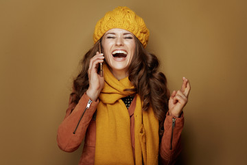 smiling modern woman with crossed fingers talking on phone