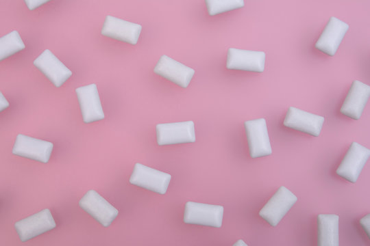 Texture of white chewing gum on a pink background. Close up. Flat lay