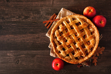 Homemade autumn apple pie, top view with frame of ingredients on a dark wood table with copy space Wall mural
