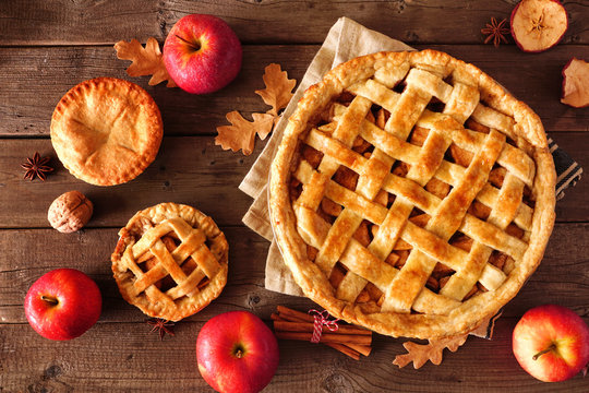 Homemade autumn apple pies, top view table scene with a rustic wood background