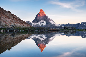 Matterhorn and reflection on the water surface during sunrise. Beautiful natural landscape. Switzerland travel - image