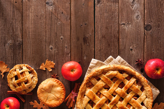 Homemade autumn apple pie bottom border. Above view table scene over a rustic wood background with copy space.