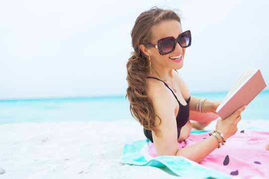 smiling elegant 40 year old woman on white beach with book