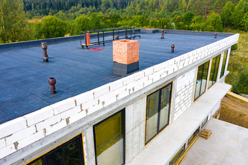 Roof waterproofing. Building construction. A protective layer was applied on the roof of the house. Installation of a waterproofing layer. Construction works. Bitumen insulating layer.