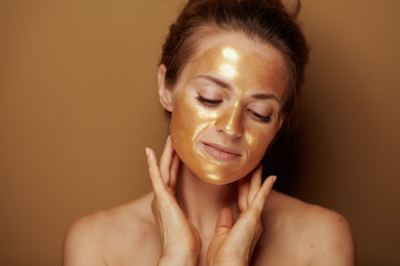 relaxed woman with golden mask against beige background