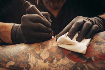 Close up tattoo machine. Tattooing. Man creating picture on his back by a professional tattoo artist.