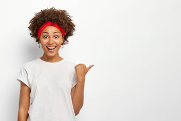 Joyful dark skinned young African American woman points away right with thumb, dressed in casual wear, demonstrates copy space for your advertising content, smiles happily, recommends something