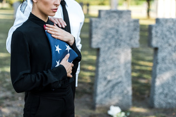 cropped view of senior man near woman with american flag on funeral Wall mural