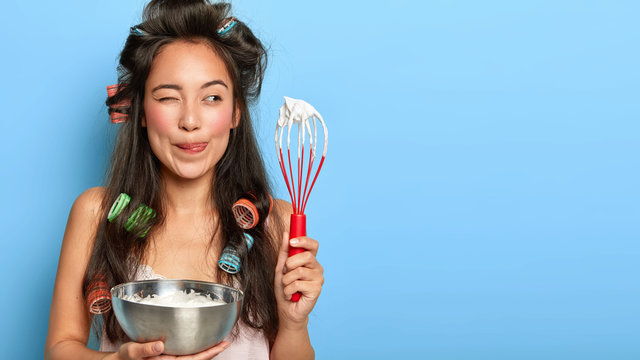 Pleased dark haired woman licks lips, enjoys sweet taste of cream, holds whisk and bowl, mixes ingredients, dressed in domestic clothes, wears curlers, focused aside, busy cooking at kitchen
