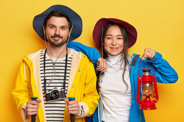 Horizontal shot of happy mixed race woman and man tourists spend summer vacation actively, walk on foot, cover long destination, male holds trekking sticks, retro camera, female with kerosene lamp