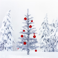 Artificial fake tinsel Christmas tree with bright red ornaments decorations outdoors in snowy winter nature landscape. Fun, modern holiday background backgrounds.