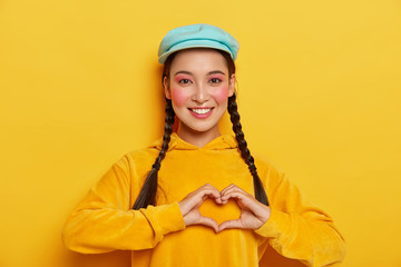 Young happy Korean woman makes heart gesture over chest, has two pigtails, wears blue cap and yellow hoody, expresses good emotions, shows love to someone, poses indoor. My heart is for you.