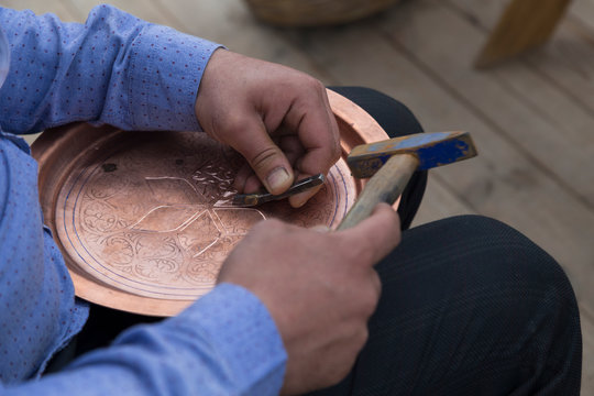 the man making pattern on the copper plate