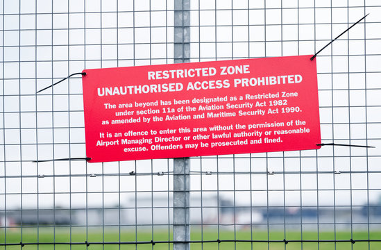 Restricted air space zone sign at airport barrier fence no unauthorised access