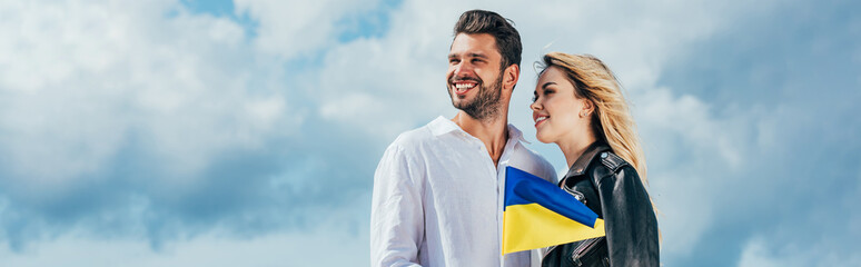 Fotomurales - panoramic shot of attractive woman and handsome man smiling and holding ukrainian flag