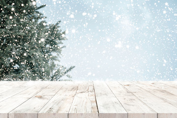 Top of empty wood table with fir tree and snowfall  backdrop. ready for your product display or montage. Concept of background in Christmas and winter holidays.