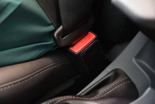 Woman sitting on car seat and fastening a seat belt. Car safety concept.