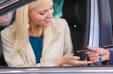 Beautiful young woman is getting key and smiling while sitting in a new car in dealership