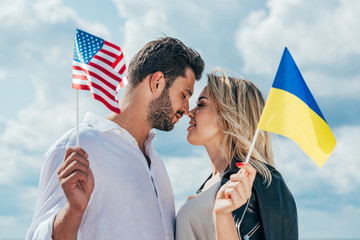 Fotomurales - attractive woman and handsome man holding american and ukrainian flags